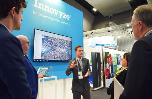 photo of Toby explaining Innovyze software to exhibition visitors